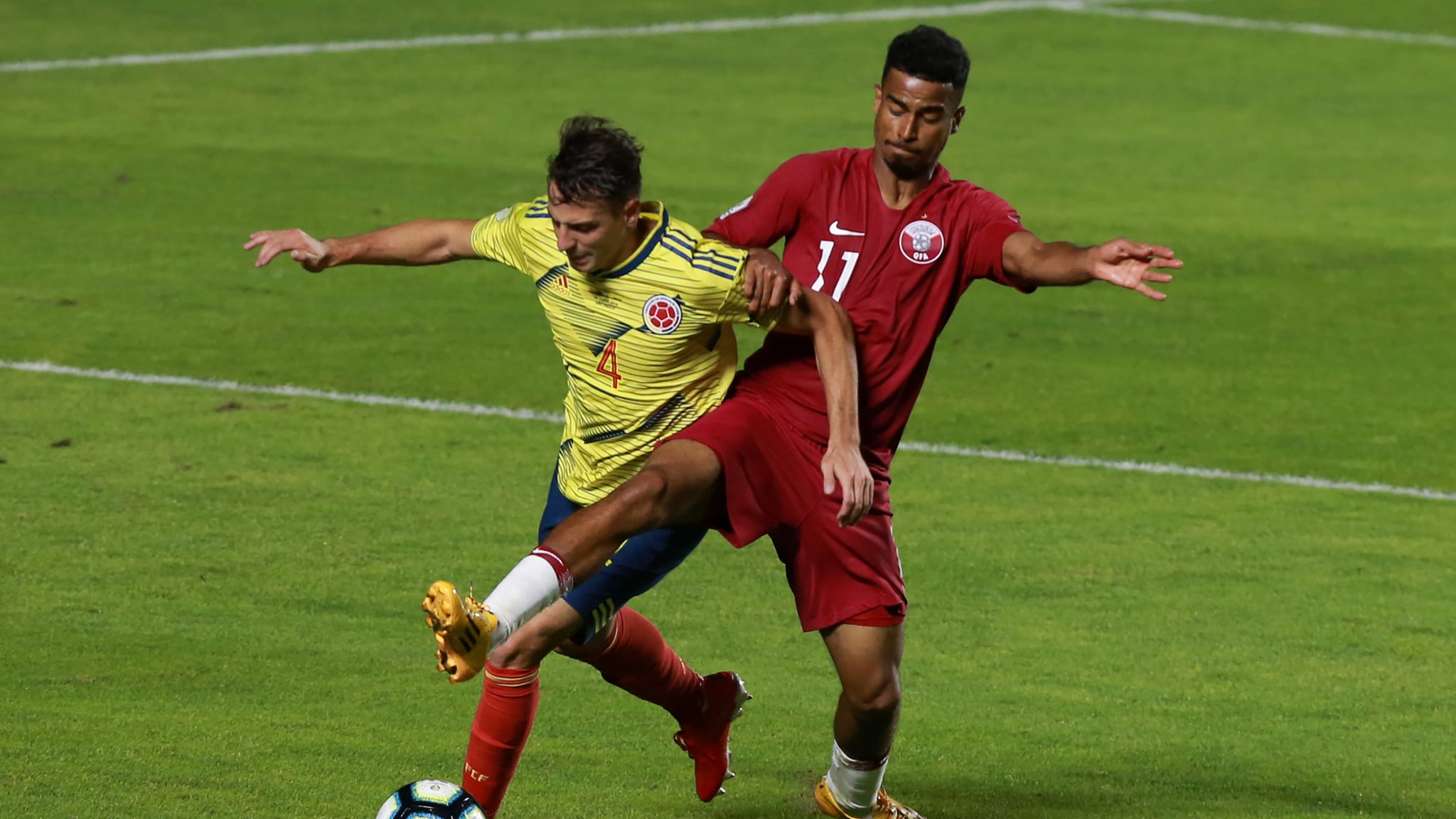 Santiago Arias of Colombia fights for the ball with Akram Afif of Qatar