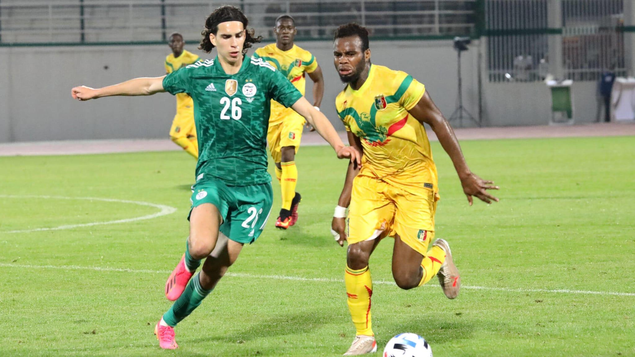 Ramiz Zerrouki (L) of Algeria in action against Mali