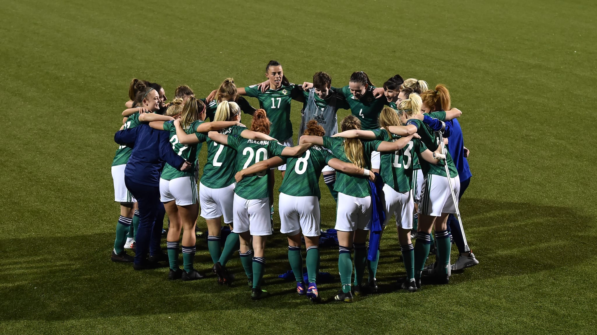 Northern Ireland players huddle on pitch, celebrating victory in the UEFA Women's Euro 2022 Play-off match between Northern Ireland and Ukraine at Seaview on April 13, 2021 in Belfast, Northern Ireland.