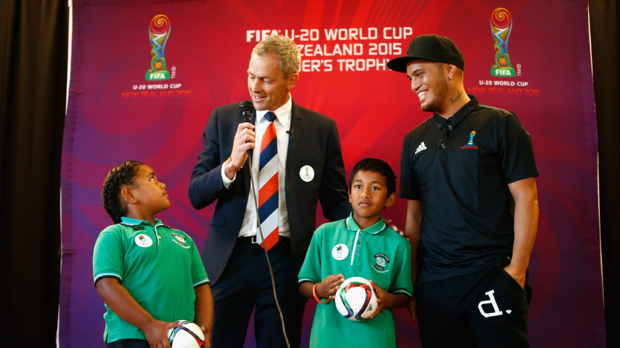 FIFA U20 World Cup CEO Dave Beeche and New Zealand musician and NZ Idol Judge Stan Walker (R) stand with school children Kazitoa Farani and Matilda Lako after Stan Walker was announced as an ambassador for the FIFA U20 World Cup