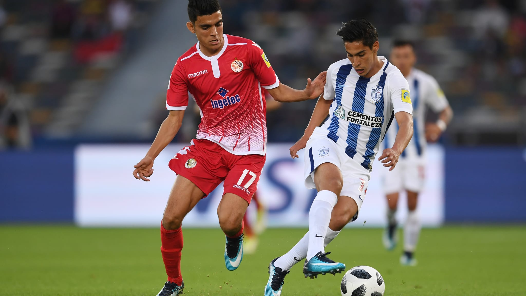 Erick Aguirre of Pachuca is challenged by Achraf Bencharki of Wydad Casablanca