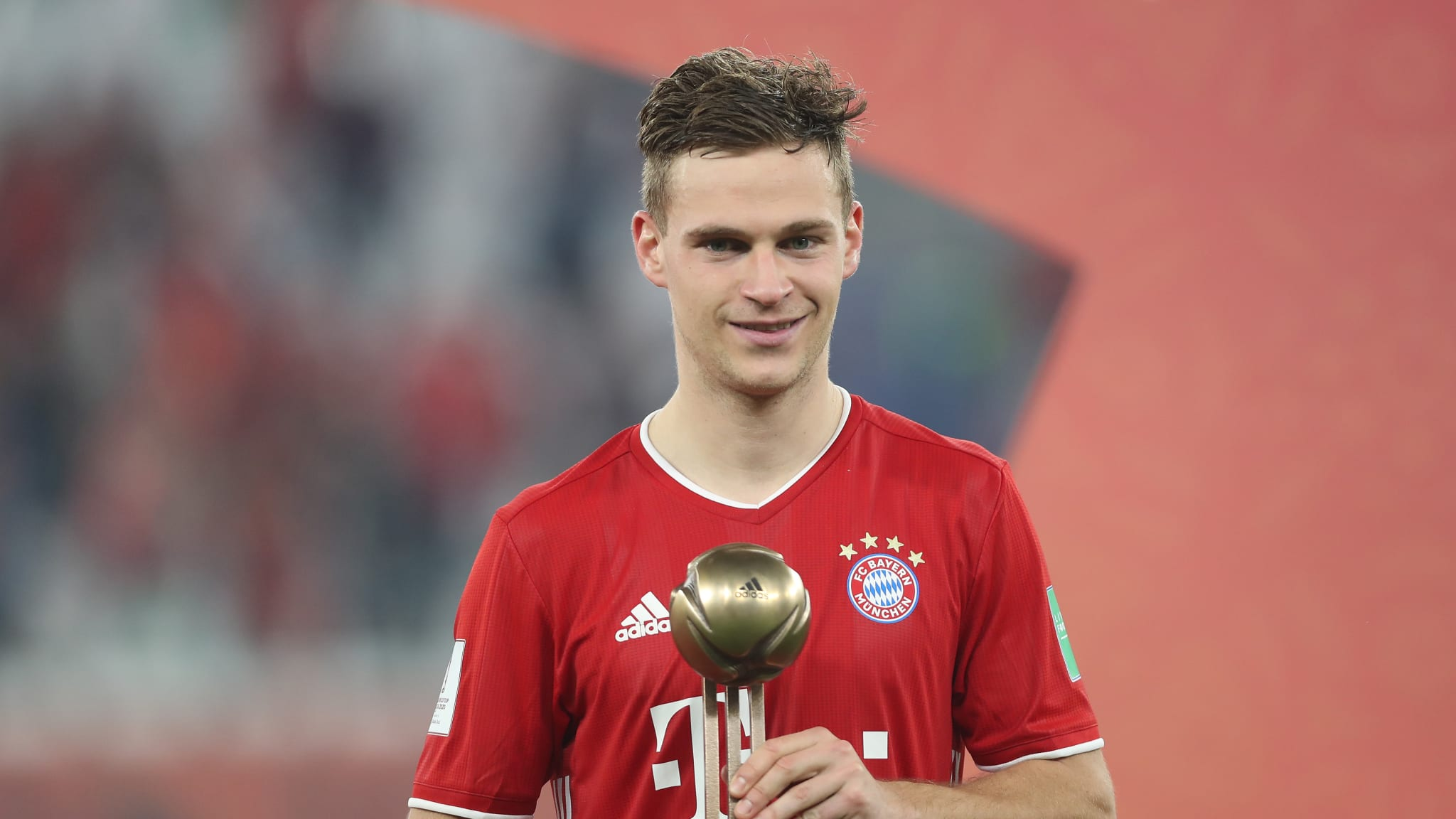 Joshua Kimmich of FC Bayern Muenchen poses with the FIFA Club World Cup Qatar 2020 adidas bronze ball trophy